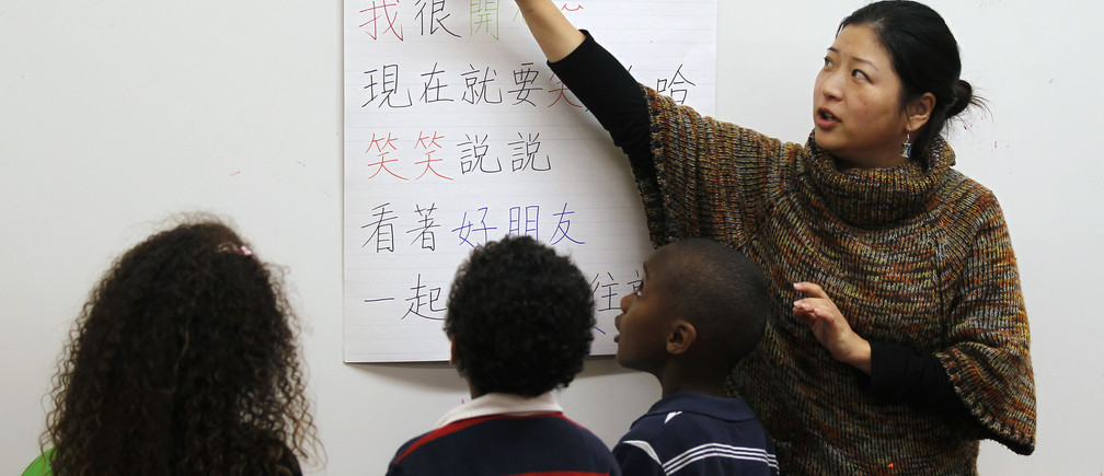 Teacher Kennis Wong (R) points to Chinese characters on a board at Broadway Elementary School in Venice, Los Angeles, California, April 11, 2011. The school launched one of only two English-Mandarin Chinese dual-language immersion programs in the Los Angeles Unified School District in September 2010.  REUTERS/Lucy Nicholson (UNITED STATES - Tags: SOCIETY EDUCATION) - GM1E74C0S3R01