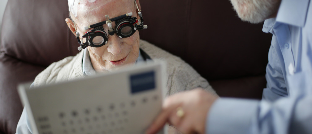 Resident Ernie Mayes, 89, has his eyes checked by Optometrist in his flat at the Colbrooke House care facility run by a private company working on behalf of the local government and housing association in southeast London February 13, 2015. The provision of care for those who can no longer look after themselves but do not require a place in hospital is one of the biggest problems facing the state-funded National Health Service. The involvement of the private sector in critical services remains a contentious issue in Britain after large outsourcers failed in previous high profile contracts. REUTERS/Suzanne Plunkett (BRITAIN - Tags: POLITICS HEALTH SOCIETY) - LM1EB2J0R3W01