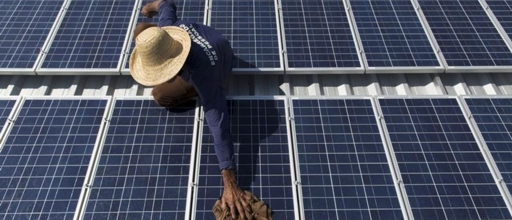 Francisco da Silva Vale, 61, cleans solar panels which power ice machines at Vila Nova do Amana community in the Sustainable Development Reserve, in Amazonas state, Brazil, September 22, 2015. Three solar-powered machines, are producing about ninety kilos of ice per day, in a region with poor access to electric energy, which used to be produced only with diesel oil, in the Amazon rain forest. The Gelo Solar (Solar Ice) project, developed by the Mamiraua Institute for Sustainable Development and the Sao Paulo University (USP), aims to improve the life quality of the residents of the communities allowing them to preserve their fish and fruits productions which are their main economic resources. The Mamiraua Institute is also using solar energy to supply the community's homes with water and light up a soccer field.