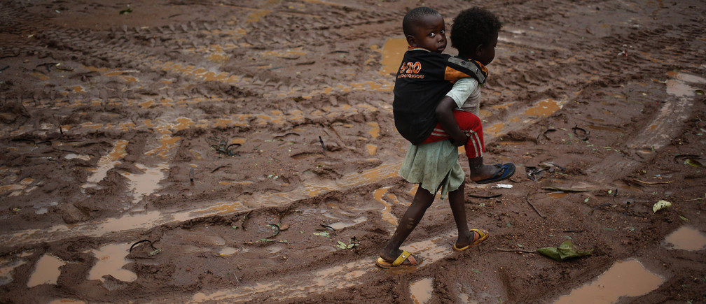 Children walk during rain in front of Saint Michel Catholic church in the town of Boda April 14, 2014.