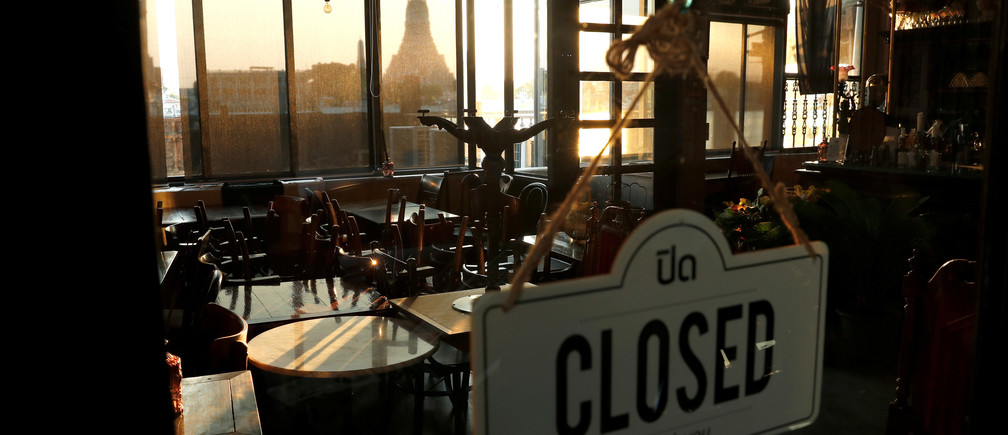 A closed restaurant due to the coronavirus disease (COVID-19) outbreak, is seen next to the Chao Phraya river with a view of Wat Arun temple, one of the city's top tourist spots, in Bangkok, Thailand March 27, 2020. REUTERS/Jorge Silva - RC2FSF9MGL9I