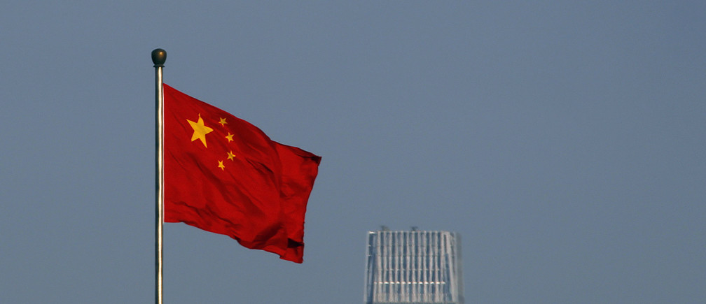 A Chinese national flag flies outside the Xinhua Gate of the Zhongnanhai leadership compound, the residence of China's top leaders, with World Trade Centre Tower III, a 330-meter-tall skyscraper, the tallest in Beijing in the background November 11, 2010. Chinese inflation sped to a 25-month high in October and bank lending blew past expectations, highlighting the challenge faced by Beijing as it battles to keep a lid on price pressures. REUTERS/Petar Kujundzic (CHINA - Tags: POLITICS BUSINESS) - GM1E6BB1EE301