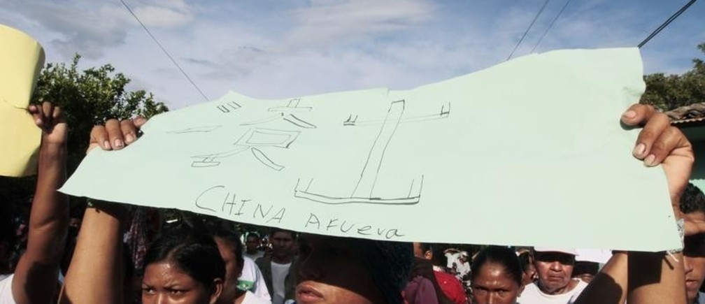 """A resident holds a sign with anti-Chinese messages during a protest march against the construction of the Interoceanic Grand Canal in Rivas September 19, 2014. Chinese businessman Wang Jing sealed a controversial no-bid 50-year renewable concession from Nicaragua's Sandinista government in 2013 to develop the $50 billion canal to rival Panama's, and related facilities. Hundreds of people marched to protest against the construction of the Interoceanic Grand Canal that they said would affect their properties. The sign reads, """"Get out"""" in Chinese, and """"China get out"""" in Spanish."""