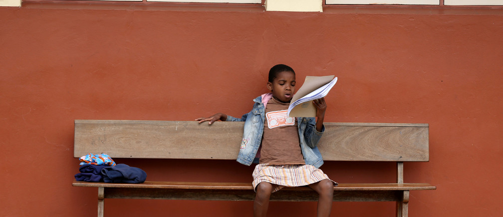 A girl reads a book at the Casa Madre Maria Clara (Mother Maria Clara House), a Christian boarding school that accommodates abandoned and orphaned children as well as children from poor backgrounds and teaches them life skills, in Lhanguene, Maputo, Mozambique, August 31, 2019. REUTERS/Siphiwe Sibeko - RC1F1230C240