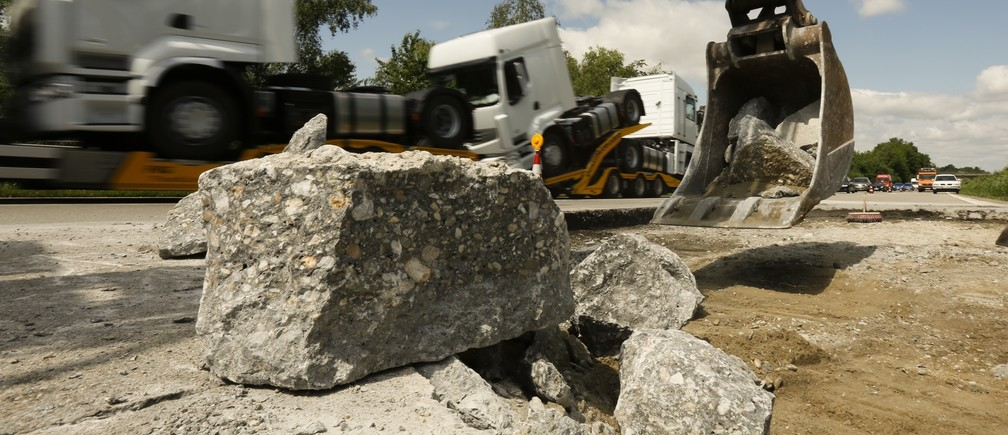 n excavator removes broken concrete parts on the A3 motorway between Deggendorf and Passau near the south eastern Bavarian town of Hengersberg June 21, 2013.