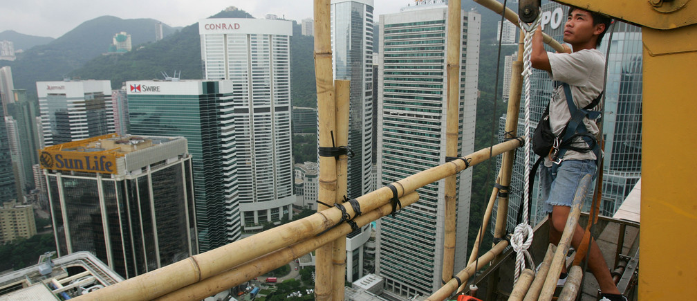 A man works on the bamboo scaffolding on the 50th floor of the Far East Finance Center in Hong Kong September 9, 2006.    REUTERS/Paul Yeung  (HONG KONG) - GM1DTLVRLGAA