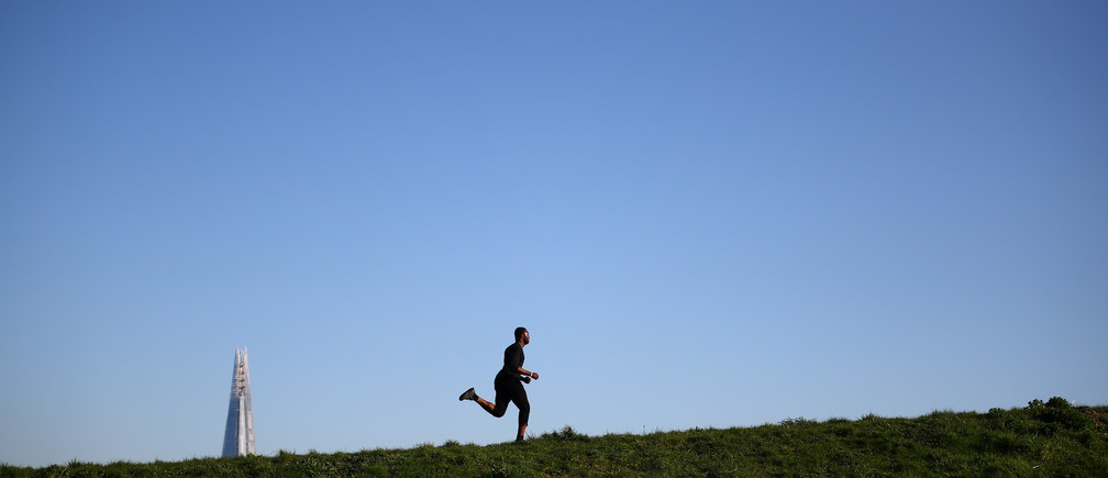 A runner is seen in Burgess Park, as the spread of coronavirus disease (COVID-19) continues in London, Britain, March 25, 2020. REUTERS/Hannah McKay - RC2WQF95Q1OV