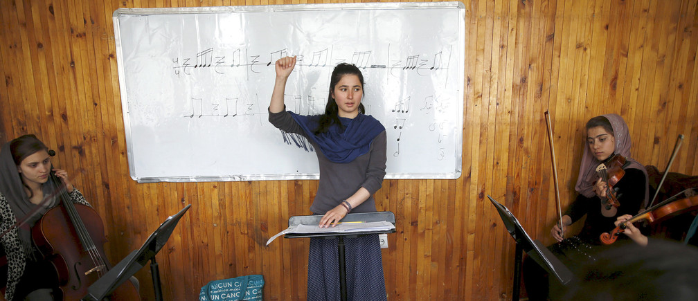 "Negin Khpulwak, leader of the Zohra orchestra, an ensemble of 35 women, conducts during a rehearsal at Afghanistan's National Institute of Music, in Kabul, Afghanistan April 9, 2016. Playing instruments was banned under Taliban rule in Afghanistan, and even today, many conservative Muslims frown on most forms of music. Living in an orphanage in the capital, Kabul, 19-year-old Negin leads an ensemble of 35 women that plays both Western and Afghan musical instruments. In a country notorious internationally for harsh restrictions on women in most areas of life, Negin's story highlights a double challenge. REUTERS/Ahmad Masood SEARCH ""ORCHESTRA KABUL"" FOR THIS STORY. SEARCH ""THE WIDER IMAGE"" FOR ALL STORIES  - GF10000383703"