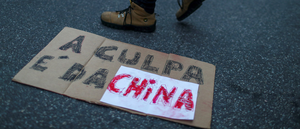 """A person walks past a sign laying on the ground that reads: """"It's China's fault"""" as supporters of Brazil's President Jair Bolsonaro take part in a protest blaming China for being the country where the coronavirus disease (COVID-19) started, in front of the Chinese consulate in Rio de Janeiro, Brazil May 17, 2020."""