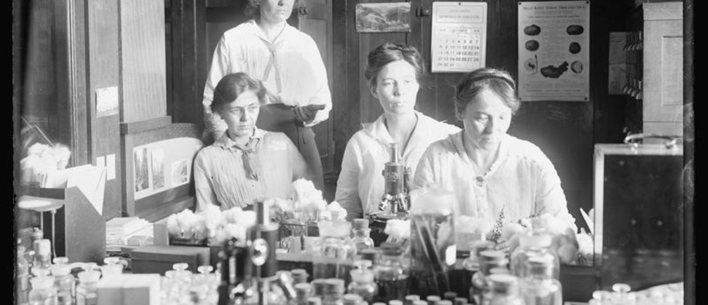 "Women scientists (standing) Miss Nellie A. Brown, (seated L-R) Miss Lucia McCollock, Miss Mary K. Bryan and Miss Florence Hedges work at a laboratory, circa 1910-1920, in this Library of Congress handout photo. For women 100 years ago, opportunities to work beyond the home and take part in political life were very limited. As the 20th century progressed, hard-won progress included gradually improved voting rights, while the upheaval of war pushed doors ajar as women worked as part of the war effort. U.S. Library of Congress archive photos show women's workplaces ranging from a flour mill in England to a coal mine in Belgium or Lincoln Motor Co.'s welding department in Detroit. International Women's Day is celebrated on March 8. REUTERS/ National Photo Company Collection/Library of Congress/Handout via Reuters SEARCH ""THE WIDER IMAGE"" FOR ALL STORIES ATTENTION EDITORS - THIS PICTURE WAS PROVIDED BY A THIRD PARTY. REUTERS IS UNABLE TO INDEPENDENTLY VERIFY THE AUTHENTICITY, CONTENT, LOCATION OR DATE OF THIS IMAGE. THIS PICTURE IS DISTRIBUTED EXACTLY AS RECEIVED BY REUTERS, AS A SERVICE TO CLIENTS. FOR EDITORIAL USE ONLY. NOT FOR SALE FOR MARKETING OR ADVERTISING CAMPAIGNS. - GF10000329671"