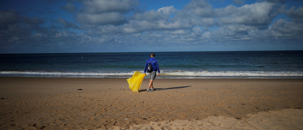 A volunteer walks as he picks up plastics, during a garbage collection, ahead of World Environment Day on La Costilla Beach, on the coast of the Atlantic Ocean in Rota, Spain June 2, 2018. REUTERS/Jon Nazca     TPX IMAGES OF THE DAY - RC1E38679580