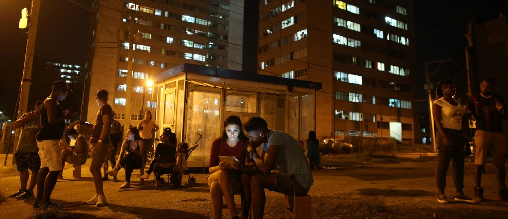 Carolina Gutierrez (center L), 17, and Neuil Valdez, 18, use mobile phones to connect to the internet at a hotspot in downtown Havana, Cuba, December 12, 2016.