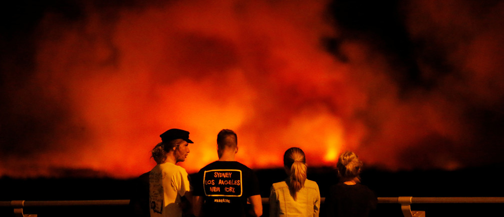 People watch a bushfire burning on the Kurnell Peninsula, during an unseasonably warm start to Spring, on Sydney's southern coast, Australia September 3, 2017. REUTERS/Jason Reed - RC157C5CAF00