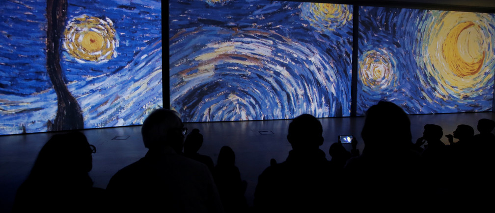 "Visitors look at a projection of details of Vincent Van Gogh's painting ""Starry Night"" at the ""Van Gogh Alive"" exhibition in Athens, Greece, November 10, 2017. Picture taken November 10, 2017. REUTERS/Alkis Konstantinidis - RC11682B72B0"