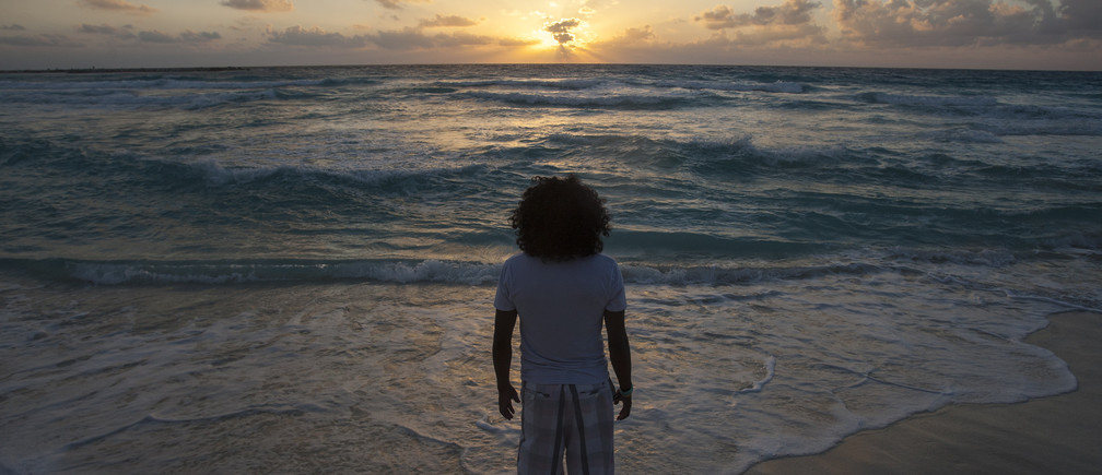 A man watches the sunrise on New Year's Day at Gaviota Azul beach in Cancun January 1, 2014.