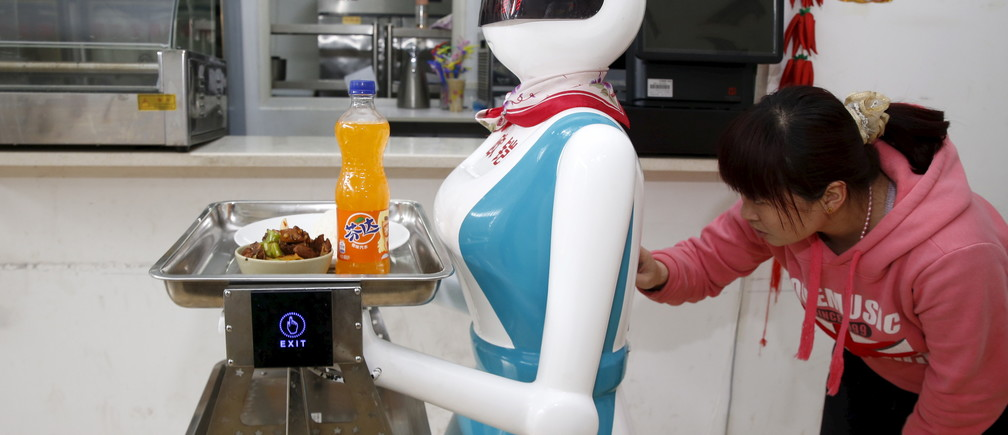 A woman input orders for a waitress robot in a restaurant in Xi'an, China