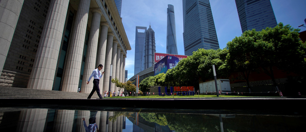 A man walks at Lujiazui financial district of Pudong in Shanghai, China July 17, 2017. REUTERS/Aly Song - RTX3BQ89