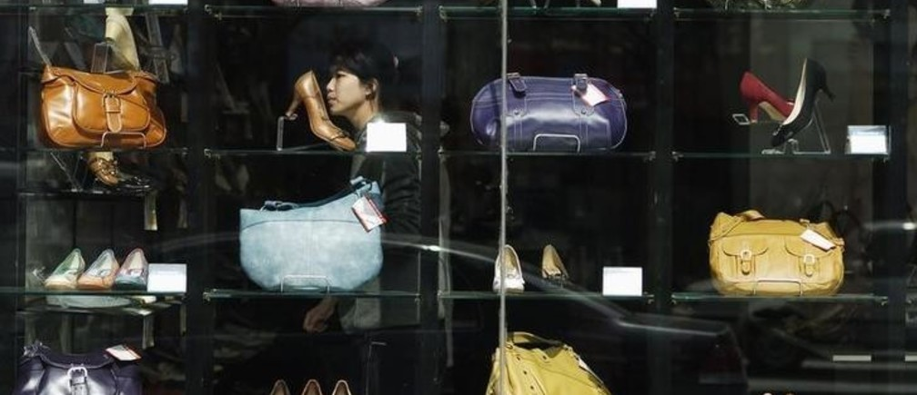 A woman passes by a shop window in Jinan, east China's Shandong province, March 9, 2007. A rapid expansion in China's retail sector and increased foreign participation in the domestic industry will herald a growing number of cases in merger and acquisitions, local media reported. CHINA OUT REUTERS/Stringer (CHINA)