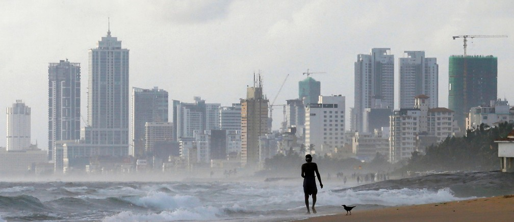 A man walks along a beach against the backdrop of Colombo's Financial City, Sri Lanka, June 2018.