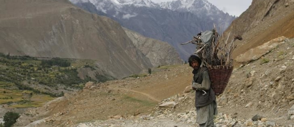 A man from the village of Askole carries firewood in the Karakoram mountain range in Pakistan August 28, 2014. Geographically, Pakistan is a climbers paradise. It rivals Nepal for the number of peaks over 7,000 meters and is home to the world's second tallest mountain, K2, as well as four of the world's 14 summits higher than 8,000 meters. In more peaceful times, northern Pakistan's unspoilt beauty was a major tourist draw but the potentially lucrative industry has been blighted by years of violence. The number of expeditions has dwindled, wrecking communities dependant on climbing for income and starving Pakistan's suffering economy of much-needed dollars. Picture taken August 28, 2014. REUTERS/Wolfgang Rattay    (PAKISTAN - Tags: ENVIRONMENT SOCIETY TRAVEL)ATTENTION EDITORS - PICTURE 13 OF 32 FOR WIDER IMAGE STORY 'K2 - THE SAVAGE MOUNTAIN' SEARCH 'RATTAY K2' FOR ALL IMAGES
