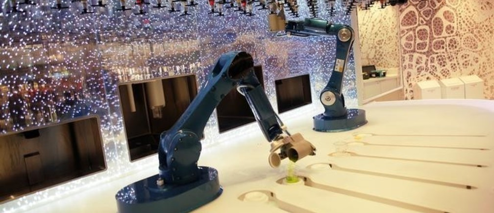 Robots serve drinks at the bionic bar, on the world's largest cruise ship of Royal Caribbean Cruises, the 362-metre-long, Symphony of the Seas, during its world presentation ceremony at a port in Malaga, Spain March 27, 2018. REUTERS/Jon Nazca