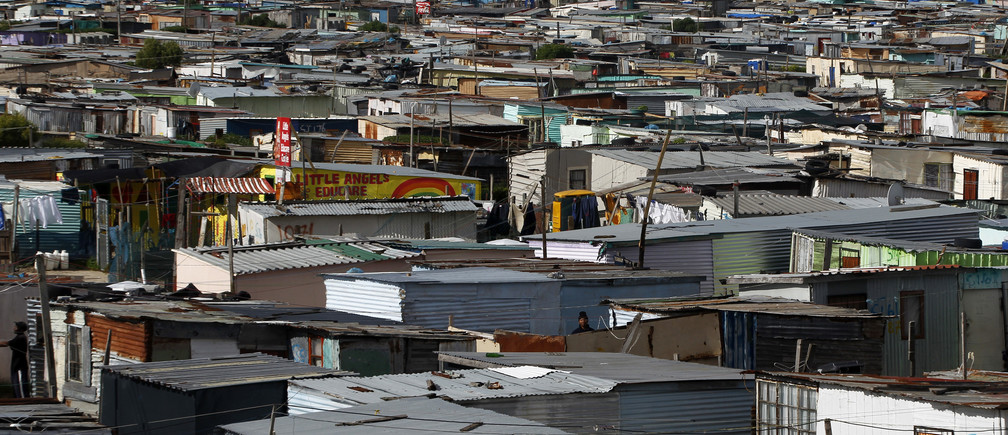 Residents walk through shacks in Cape Town's crime-ridden Khayelitsha township in this picture taken July 9, 2012. At least 11 people have died at the hands of vigilantes in the township since January as angry residents, tired of poor policing, take the law into their own hands. Picture taken July 9, 2012. To match Feature SAFRICA-CRIME/ REUTERS/Mike Hutchings (SOUTH AFRICA - Tags: CRIME LAW) - GM1E87C1UFL01