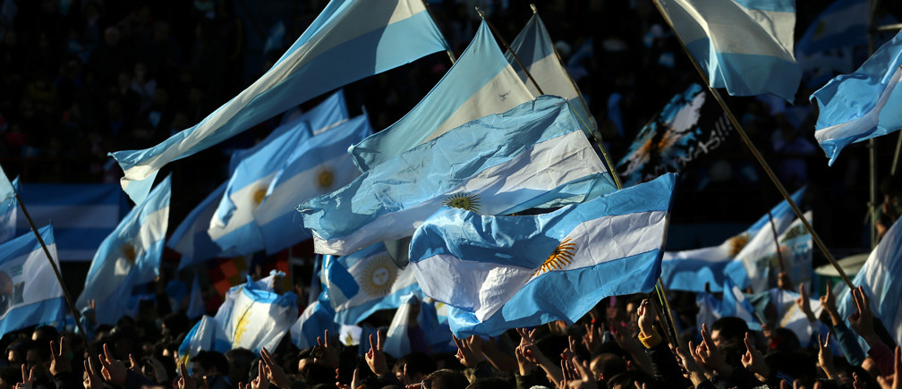 Supporters of former Argentine President Cristina Fernandez de Kirchner flash the victory sign and wave Argentine national flags as they attend a rally to commemorate flag day in Buenos Aires, Argentina June 20, 2017. REUTERS/Marcos Brindicci - RTS17XPG