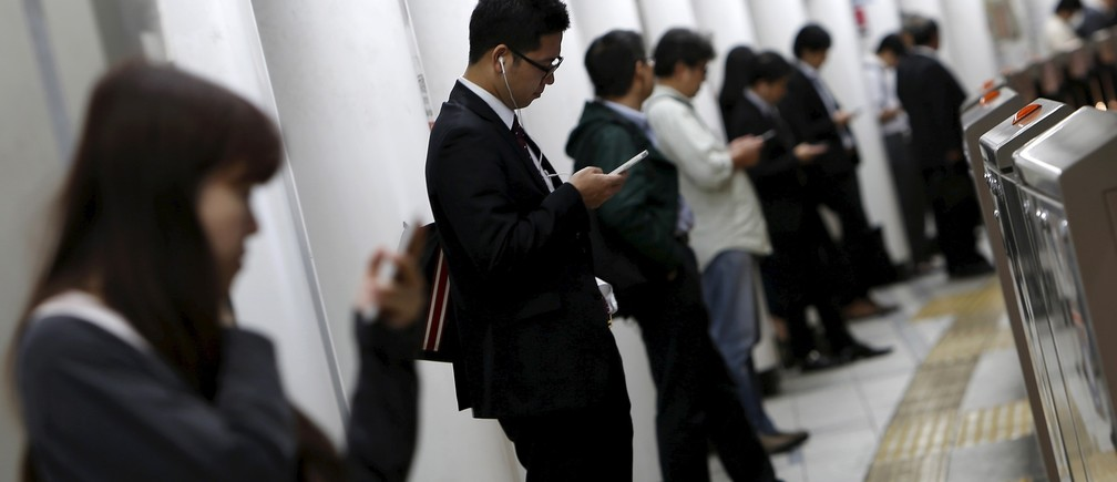 People look at their mobile phones while waiting for a train at a subway station in Tokyo, Japan, October 14, 2015.