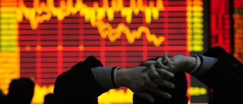 An investor looks at an electronic board showing stock information at a brokerage house in Hefei, Anhui province December 9, 2008. China's stock market dropped in heavy trade on Tuesday, led by property and financial shares, on worries that November economic data, to be released in coming days, would be poor.