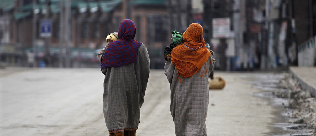 Kashmiri Muslim women carry their babies while walking through a deserted road as authorities imposed restrictions in Srinagar February 9, 2014. Authorities imposed restrictions across Srinagar as separatists called for a three-day shutdown to demand the remains of Mohammad Afzal Guru, a Kashmiri man who was executed on February 9, 2013, for an attack on India's parliament in 2001, local media reported on Sunday. REUTERS/Danish Ismail (INDIAN-ADMINISTERED KASHMIR - Tags: CIVIL UNREST POLITICS SOCIETY) - GM1EA291D1601