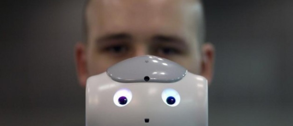 A competitor holds up one of his soccer-playing robots for the camera during the Robocup tournament in Singapore