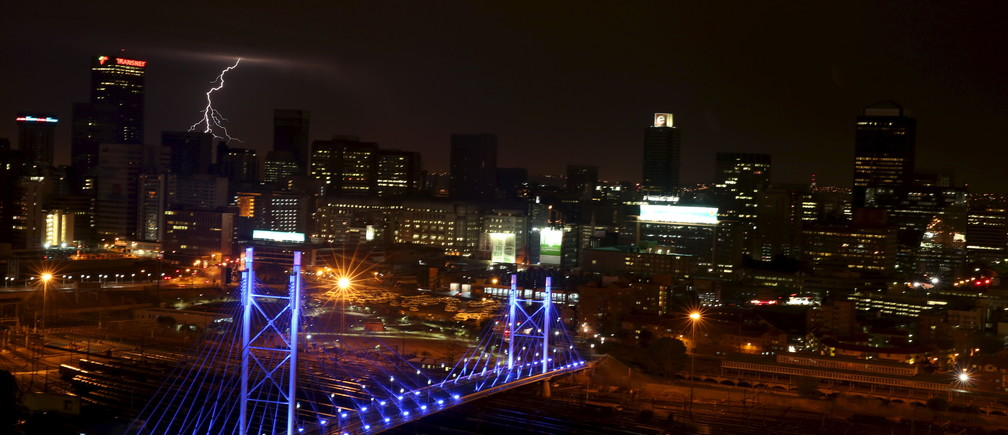 Lighting flashes in the sky over the Nelson Mandela Bridge, a Johannesburg landmark, as it is lit up in blue to mark the 70th anniversary of the United Nations, in South Africa October 24, 2015. REUTERS/Siphiwe Sibeko - GF20000031498