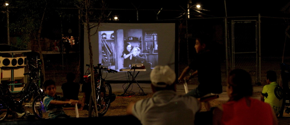 Residents watch a film projected by the Cinecleta, Moviebike, at a park in Saltillo, Mexico, September 6, 2015. Reginaldo Chapa modified a cargo bike to create the Cinecleta, a pedal-driven vehicle that carries a solar powered battery, a projector and sound equipment which it's aimed to promote clean energy and to take films and music to rough neighbourhoods in this industrial city, local media reported. Picture taken September 6, 2015. REUTERS/Daniel Becerril  - GF10000199178