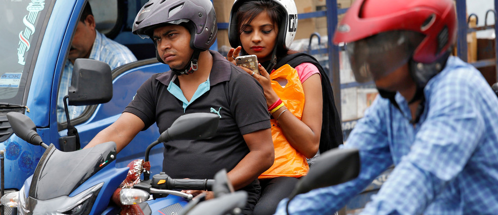 A woman checks her mobile phone at a traffic junction in Kolkata, India July 5, 2017. REUTERS/Rupak De Chowdhuri - RC17240A8A40