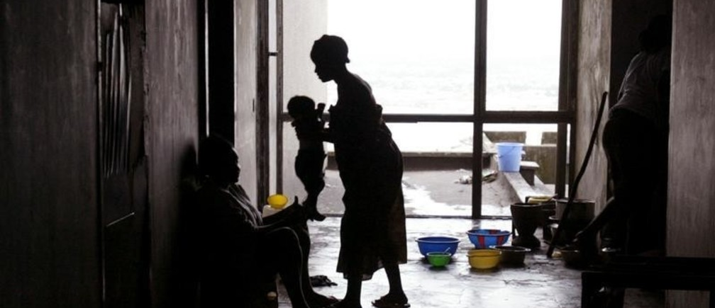 Eighteen year old Priscilla Sally (R) hands her daughter to neighbour Jackie Grimes while they stand in the corridor of the Ducor Hotel in Monrovia November 23, 2005. The former Liberian hotel has been abandoned since 1990 a year after the start of Liberia's first civil war. Several displaced families now live In the hotel. REUTERS/Luc Gnago - RP2DSFIDSPAC