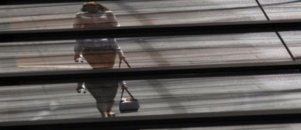 An office worker is reflected on the roof of a building.