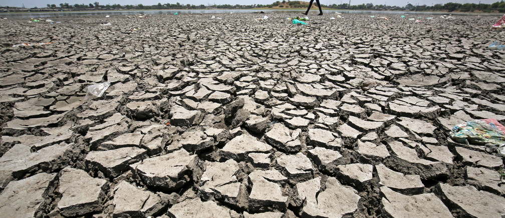 A man walks on a dried-up portion of Chandola Lake on the occasion of Earth Day, in Ahmedabad, India, April 22, 2018. REUTERS/Amit Dave - RC16ABB13CD0