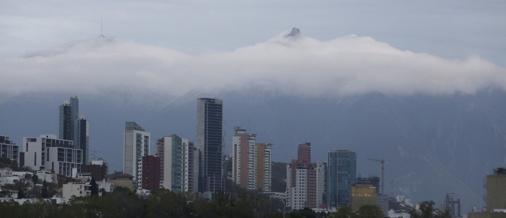 The Cerro de la Silla mountain is seen in the background during cloud cover over Monterrey skyline after a rare snow storm fell in early hours on the outskirts of Monterrey, Mexico, January 27, 2016. REUTERS/Daniel Becerril - RTX24BLV