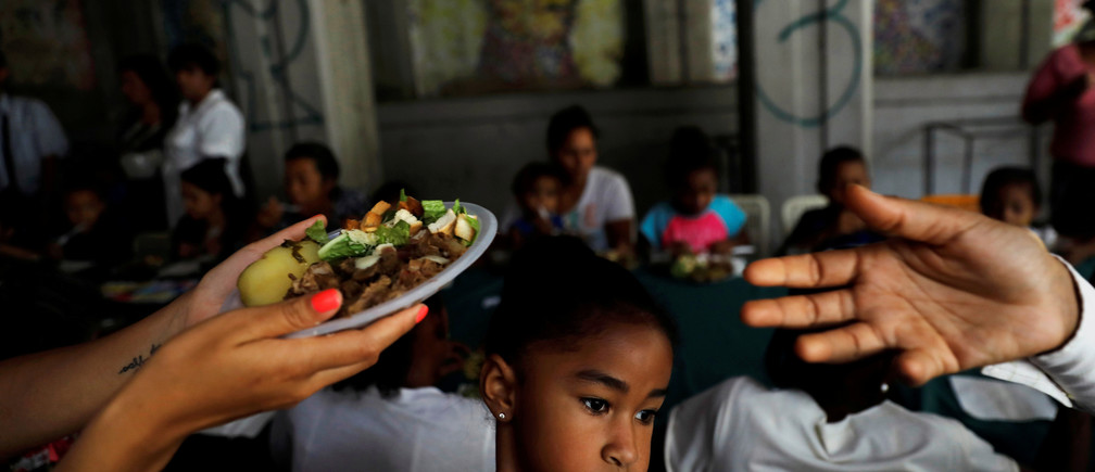 """A child looks on, as volunteers of Venezuelan presidential candidate Javier Bertucci of the """"Esperanza por el Cambio"""" party, give food plates to women and children as part of the Mothers day celebration, during a campaign rally in Caracas, Venezuela May 13, 2018. REUTERS/Carlos Jasso     TPX IMAGES OF THE DAY - RC1F9FA084F0"""
