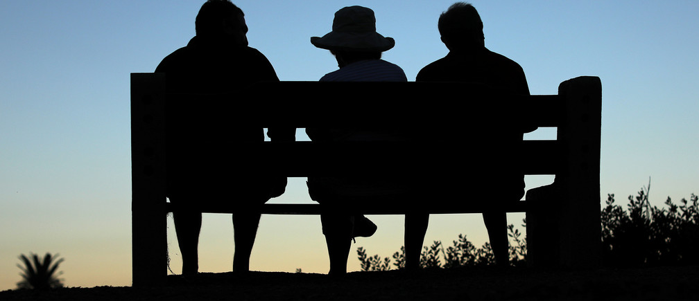 Elderly people sit on a park bench after sun set in Encinitas, California, U.S., July 5, 2017. Picture taken July 5, 2017. REUTERS/Mike Blake - RC1B80CC7FF0