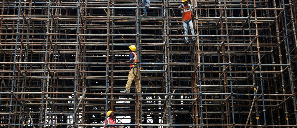 Labourers work at a construction site of a metro rail station in Kolkata, India.