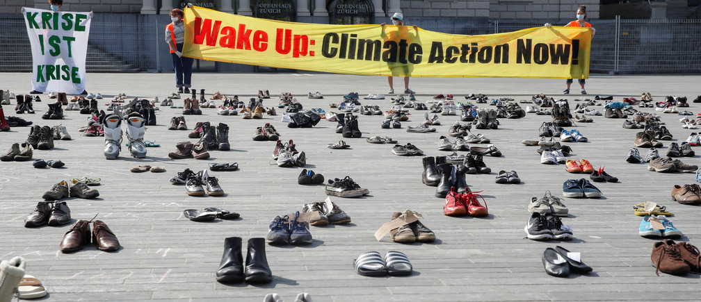 "Environmental activists of Swiss Klimastreik Schweiz movement hold banners, one of them reads: ""Crisis is crisis"", after placing shoes in place of live participants to demonstrate against climate change, as the spread of the coronavirus disease (COVID-19) continues, in front of the opera house on the Sechselaeutenplatz square in Zurich, Switzerland April 24, 2020.  REUTERS/Arnd Wiegmann - RC2YAG9410MM"