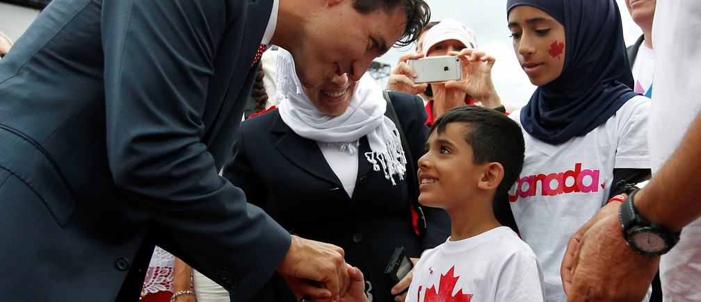 Canada's Prime Minister Justin Trudeau shakes hands with a Syrian refugee during Canada Day celebrations on Parliament Hill in Ottawa, Ontario, Canada, July 1, 2016. REUTERS/Chris Wattie - D1BETNCYGWAA