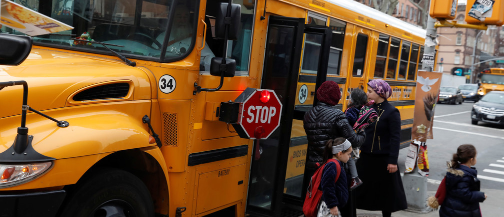 Orthodox Jewish children get off a Yeshiva school bus, as New York City Mayor Bill de Blasio declared a public health emergency in parts of Brooklyn in response to a measles outbreak, in the Williamsburg neighborhood of Brooklyn in New York City, U.S., April 9, 2019. REUTERS/Shannon Stapleton - RC188F6815D0
