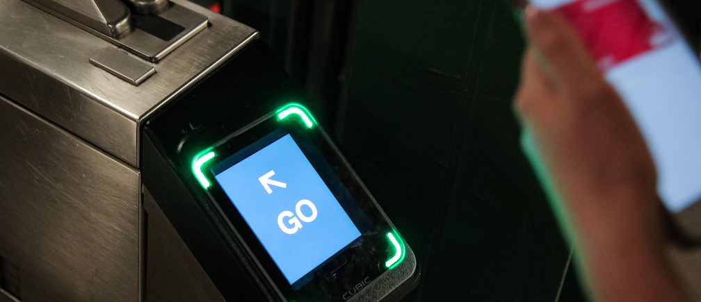 A customer uses a phone to pay for a New York City subway ride on the first day of operation of the OMNY (One Metro NY) contactless payment system in New York, U.S., May 31, 2019
