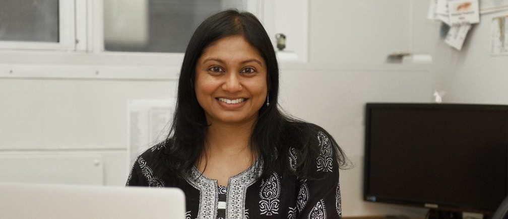 Dr Sheetal Silal smiles, sitting behind a computer at a desk in her office at the University of Cape Town.