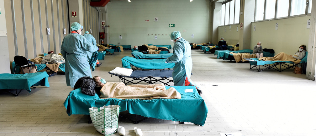 Medical personnel wearing protective face masks help patients inside the Spedali Civili hospital in Brescia, Italy March 13, 2020