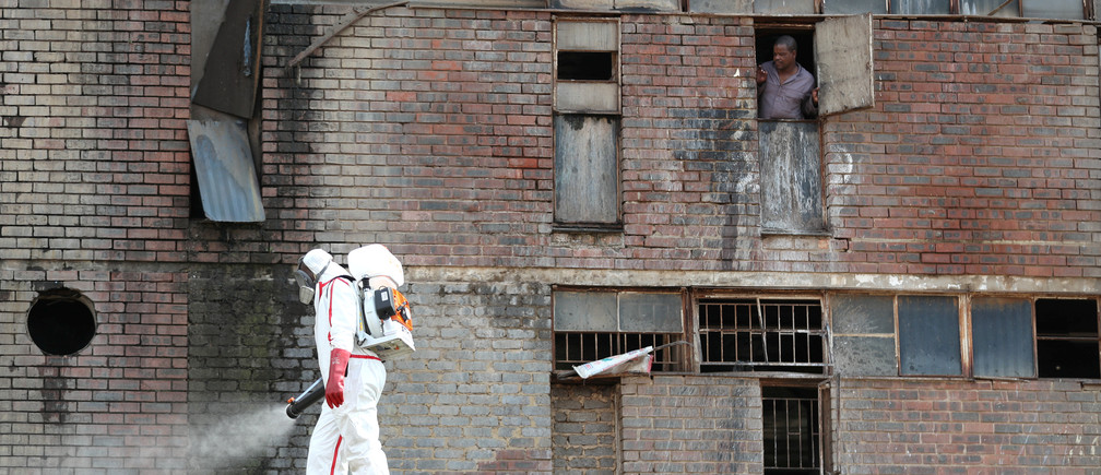 A resident looks out of the window as a worker wearing protective gear sprays disinfectant to sanitise parts of Madala Men's Hostel during a 21-day nationwide lockdown to try to contain the coronavirus disease (COVID-19) outbreak, in Alexandra, South Africa April 1, 2020. REUTERS/Siphiwe Sibeko - RC2QVF9615M1