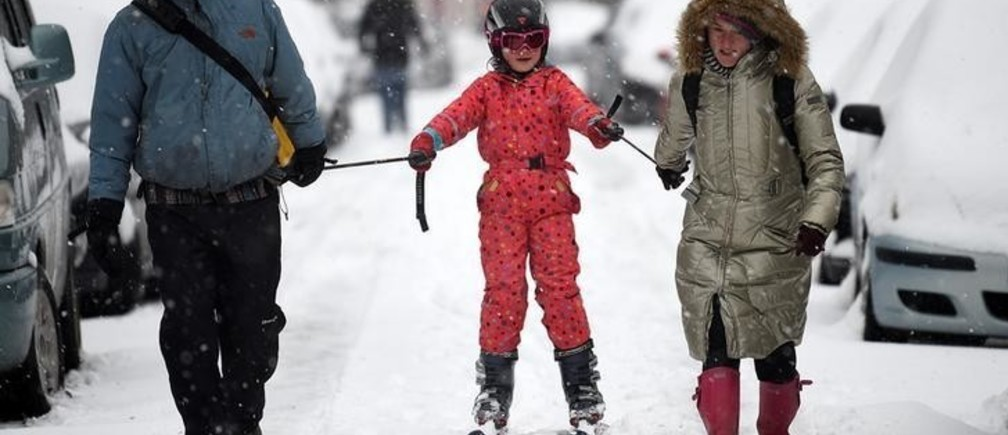 Parents use a ski to go for a walk with their child after schools closed due to adverse weather conditions in Dublin, Ireland, March 2, 2018. REUTERS/Clodagh Kilcoyne