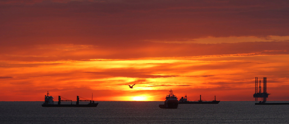 A seagull flies by as cargo ships and an offshore supply vessel lie at anchor at sunrise off Sousse, Tunisia February 14, 2018. Picture taken February 14, 2018.  REUTERS/Darrin Zammit Lupi - RC1D9A6296F0